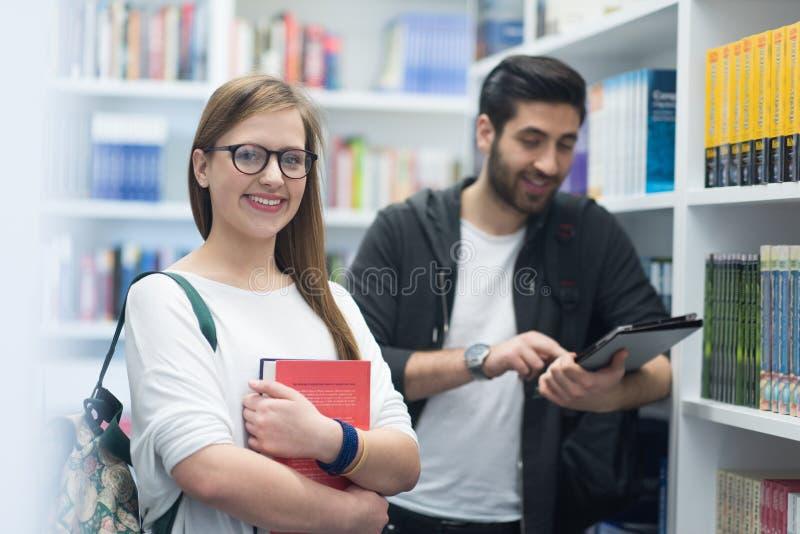 Grupo de estudantes na biblioteca escolar fotografia de stock royalty free