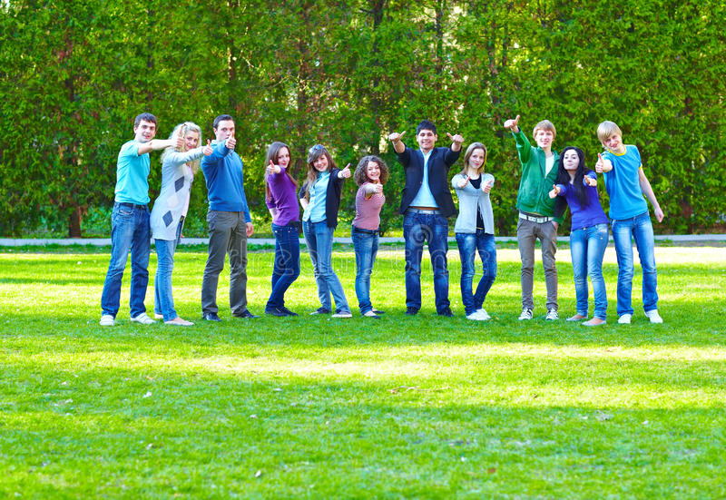 Grupo de estudantes na grama fotos de stock