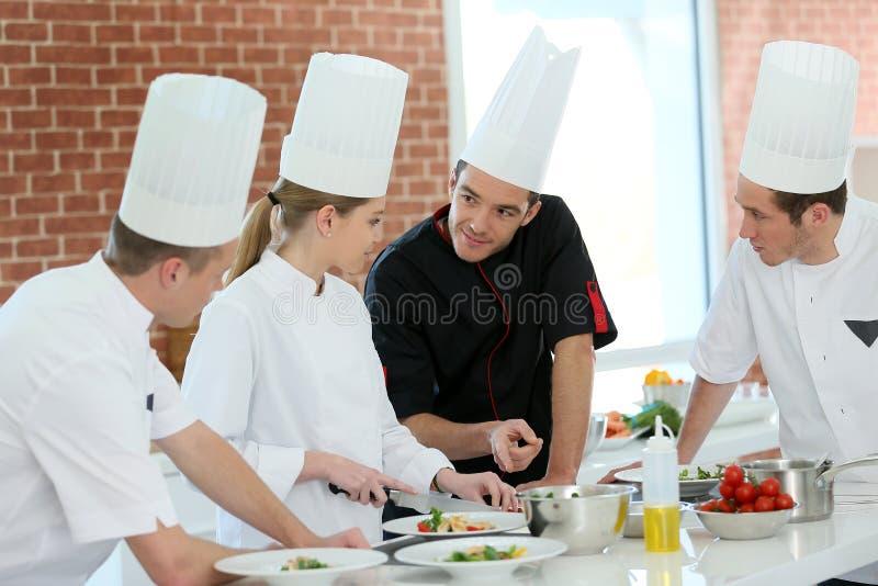 Grupo de estudantes no treinamento que cozinham o curso fotos de stock