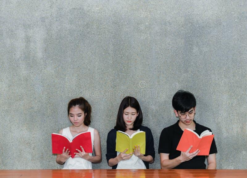 Grupo de estudantes novo que sorri olhando o livro dos dobradores da escola foto de stock