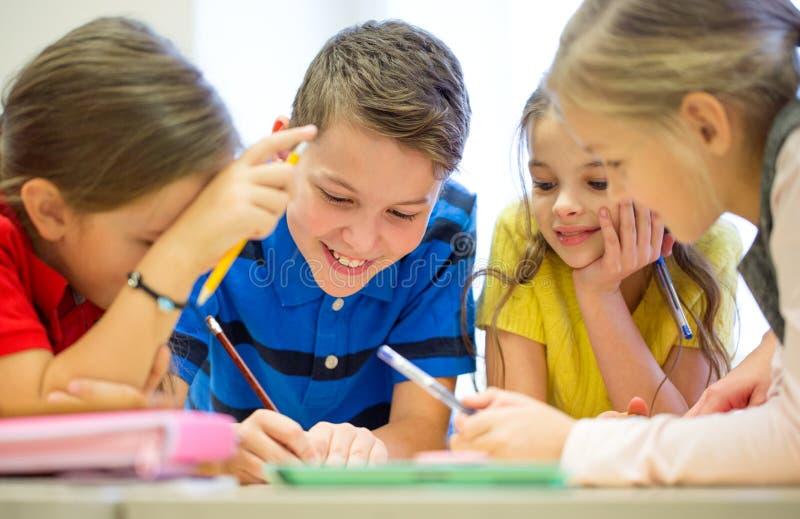Grupo de estudantes que falam e que escrevem na escola fotografia de stock