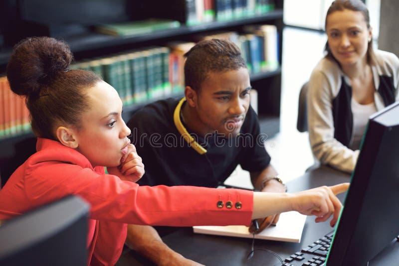 Grupo de estudantes que fazem a pesquisa em linha na biblioteca fotos de stock royalty free