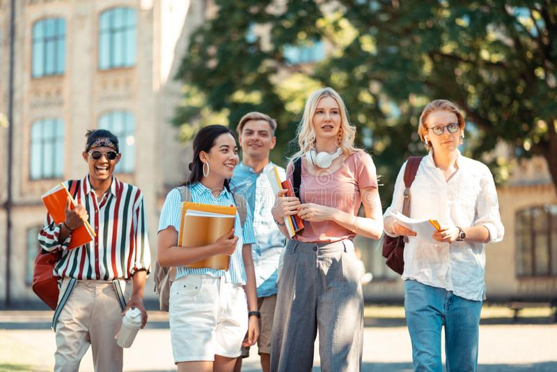 Grupo de estudantes que olham junto em seus groupmates foto de stock