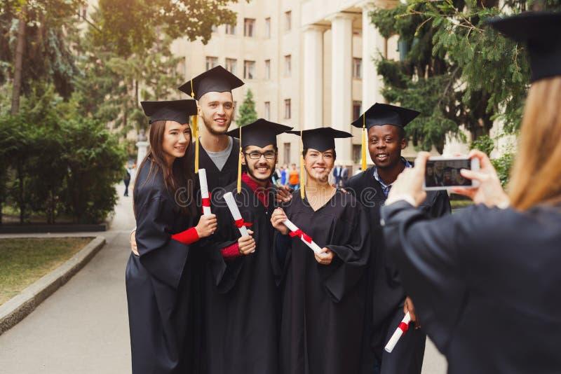 Grupo de estudantes que tomam a foto no dia de graduação fotos de stock royalty free