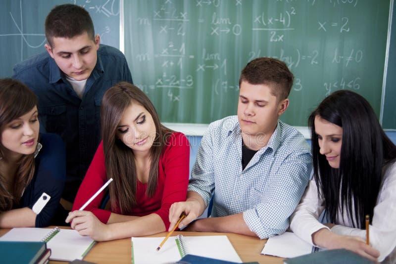 Grupo de estudantes que trabalham junto na sala de aula imagens de stock royalty free