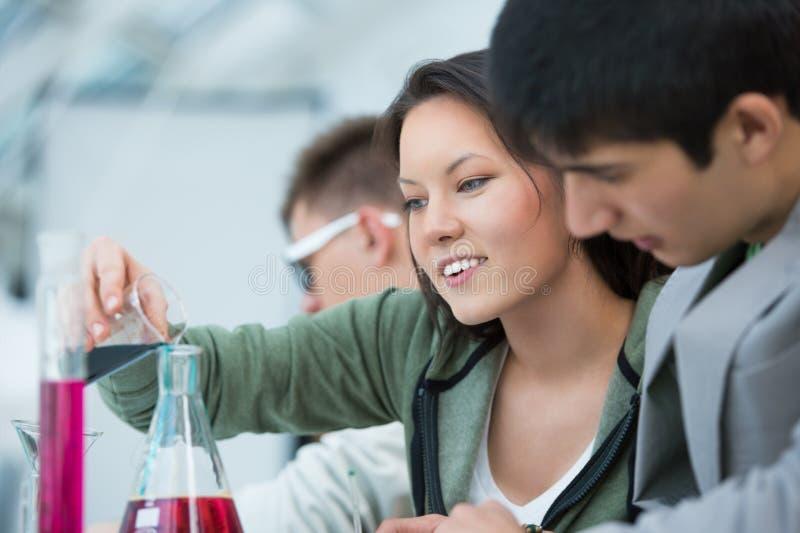 Grupo de estudantes que trabalham na sala de aula da química imagens de stock