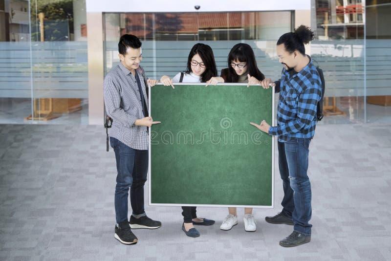 Grupo de estudantes universitário que apontam na placa verde com espaço da cópia fotos de stock