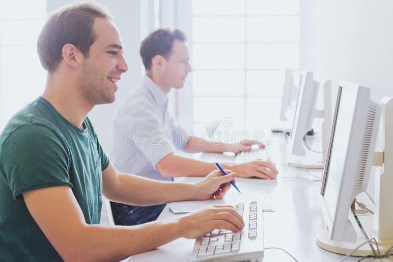 Grupo de estudantes universitário que trabalham com computadores fotos de stock royalty free