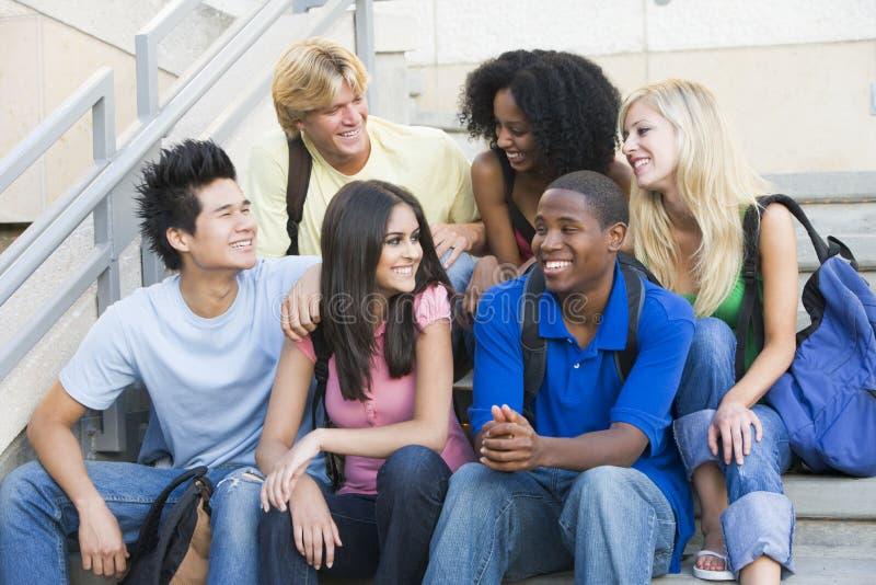 Grupo de estudantes universitários que sentam-se em etapas foto de stock