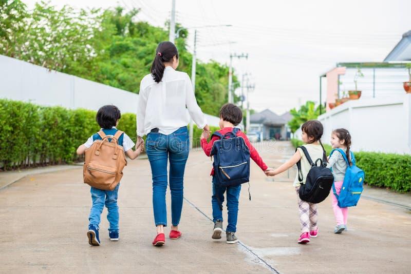 Grupo de estudiante preescolar y de profesor que celebran las manos y caminar foto de archivo