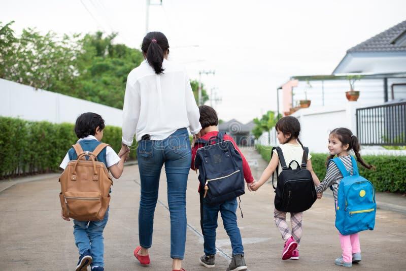 Grupo de estudiante preescolar y de profesor que llevan a cabo las manos y que caminan para dirigirse Mam? traer a sus ni?os ir a foto de archivo