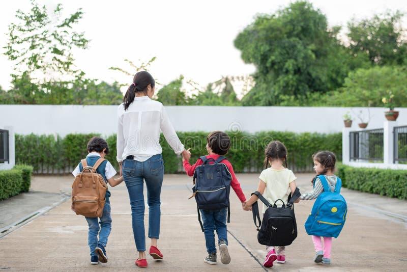 Grupo de estudiante preescolar y de profesor que llevan a cabo las manos y que caminan para dirigirse Mam? traer a sus ni?os ir a fotografía de archivo