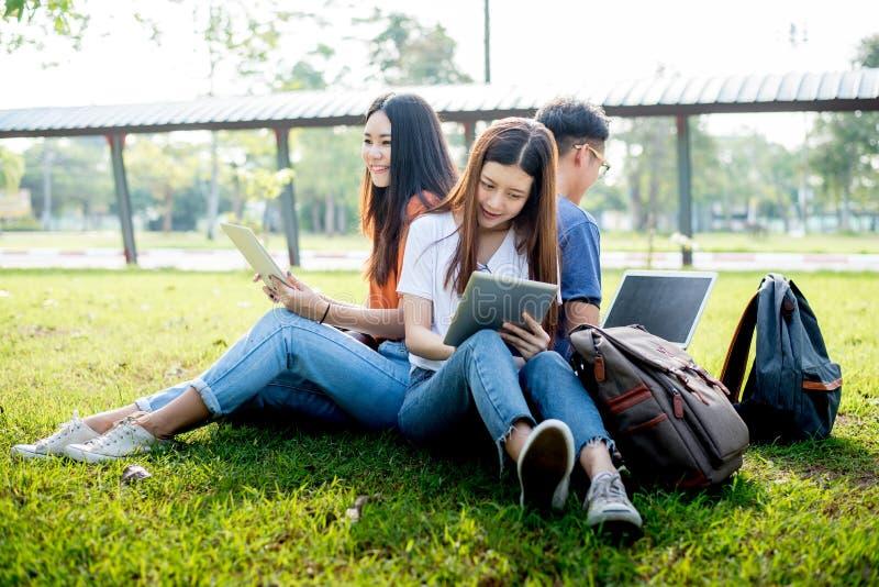 Grupo de estudiante universitario asi?tico que usa la tableta y el ordenador port?til en campo de hierba en al aire libre Tecnolo fotos de archivo