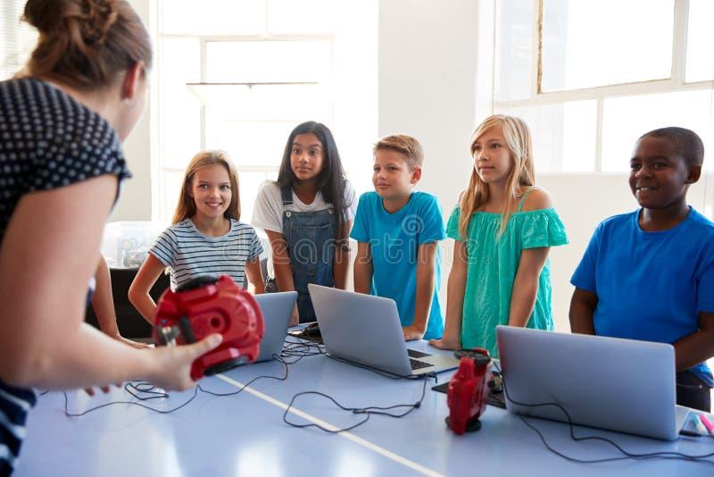 Grupo de estudiantes adentro después de la clase de la codificación del ordenador de la escuela que aprende al vehículo del robot imagenes de archivo