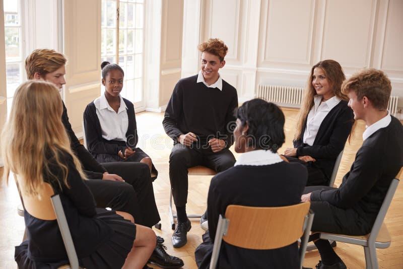 Grupo de estudiantes adolescentes que tienen discusión en clase junto fotos de archivo libres de regalías