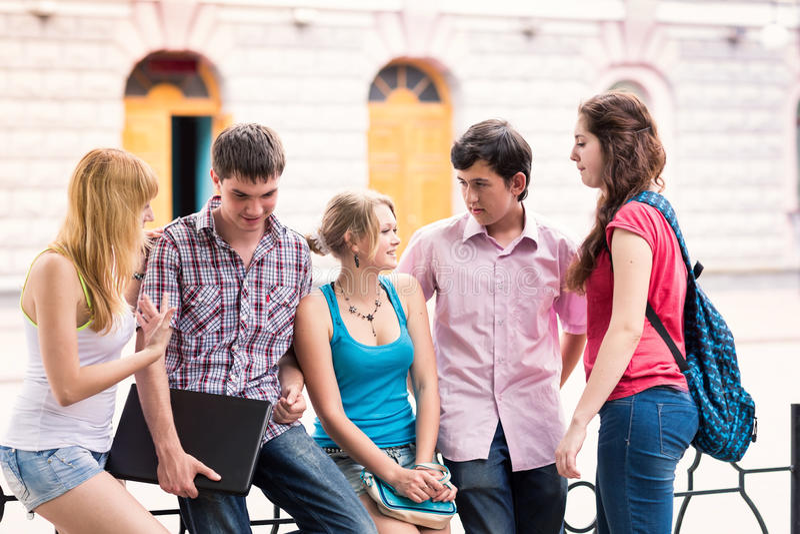 Grupo de estudiantes adolescentes sonrientes felices fuera de la universidad imagen de archivo libre de regalías