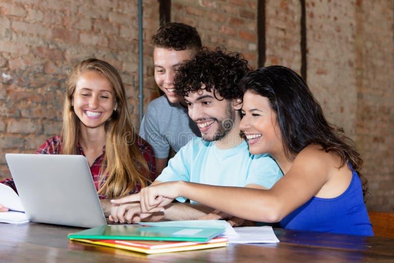 Grupo de estudiantes caucásicos jovenes que trabajan con el ordenador portátil fotos de archivo libres de regalías