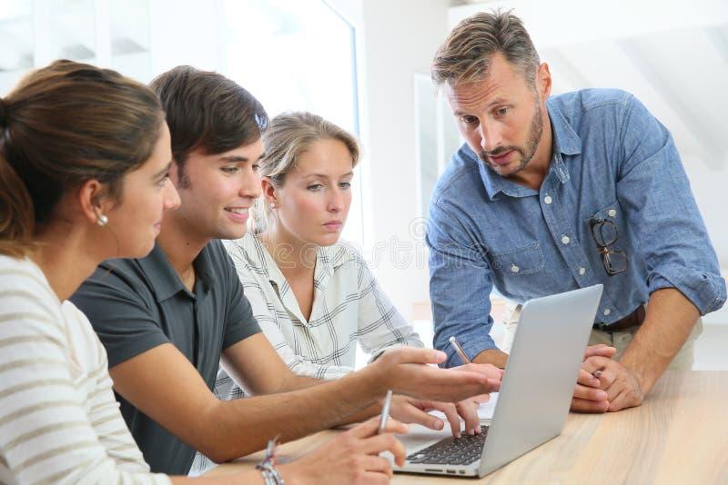 Grupo de estudiantes con el profesor que trabaja en el ordenador portátil imagen de archivo