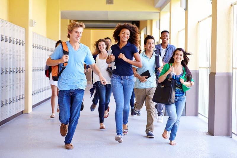 Grupo de estudiantes de la High School secundaria que corren en pasillo fotografía de archivo libre de regalías