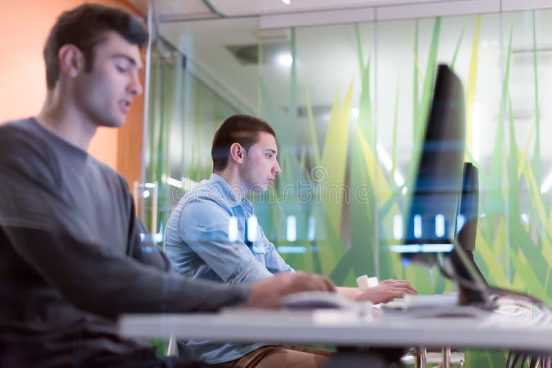Grupo de estudiantes de la tecnología que trabaja en clase de escuela del laboratorio del ordenador fotografía de archivo