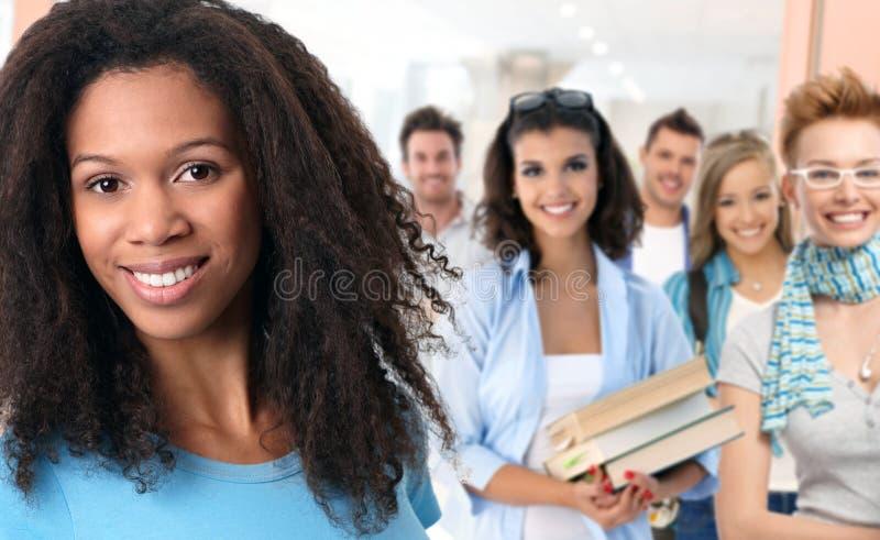 Grupo de estudiantes felices en el pasillo de la escuela imagenes de archivo