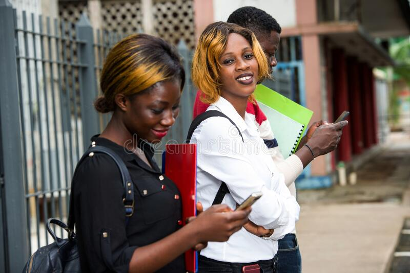 Grupo de estudiantes frente al edificio de la universidad imágenes de archivo libres de regalías