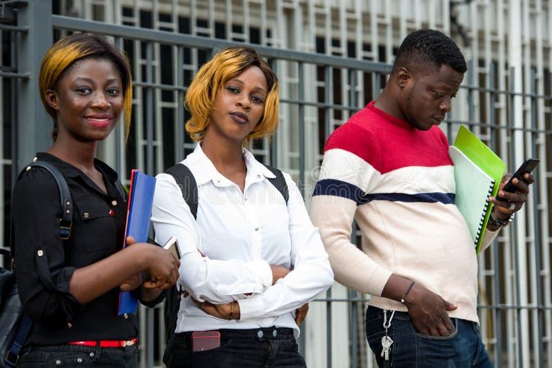 Grupo de estudiantes frente al edificio de la universidad foto de archivo