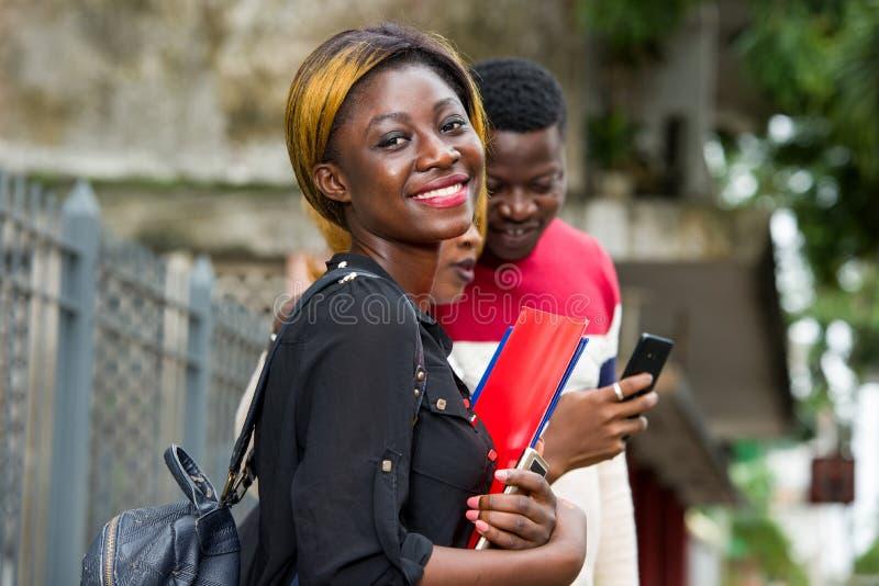 Grupo de estudiantes jóvenes de pie en la ciudad foto de archivo