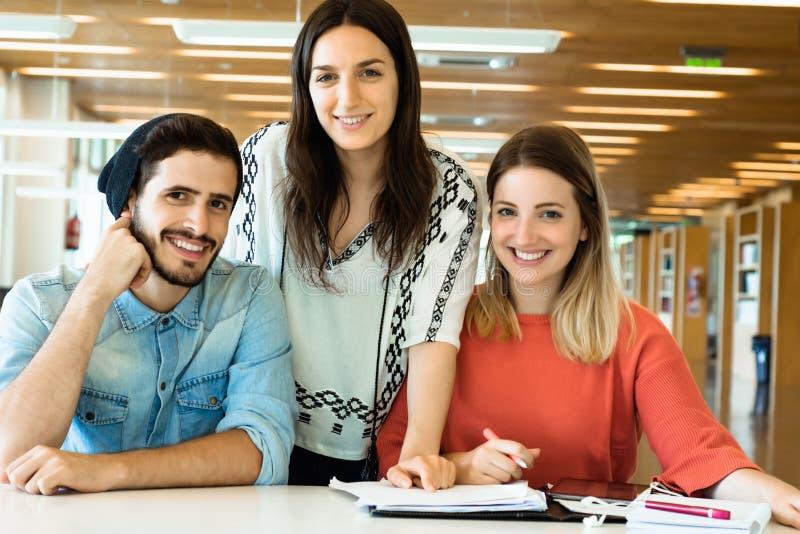 Grupo de estudiantes jovenes que estudian junto en biblioteca imagen de archivo