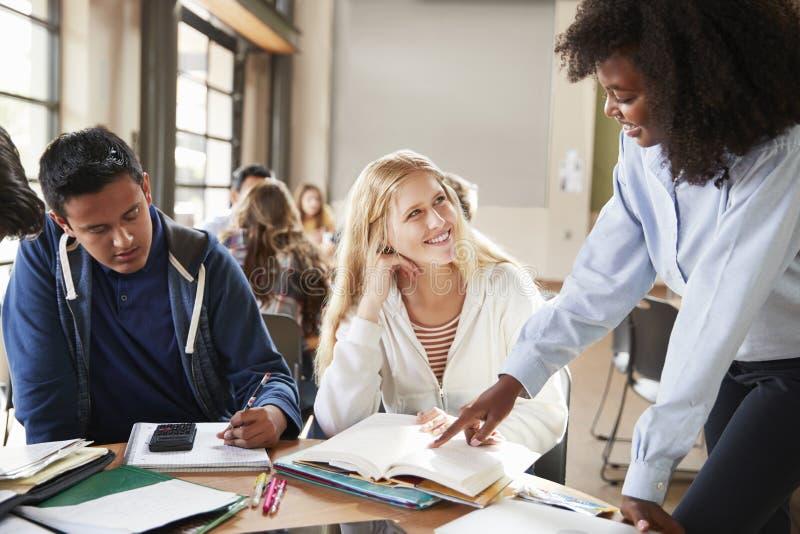 Grupo de estudiantes de la High School secundaria con el profesor de sexo femenino Working At Desk imagen de archivo libre de regalías