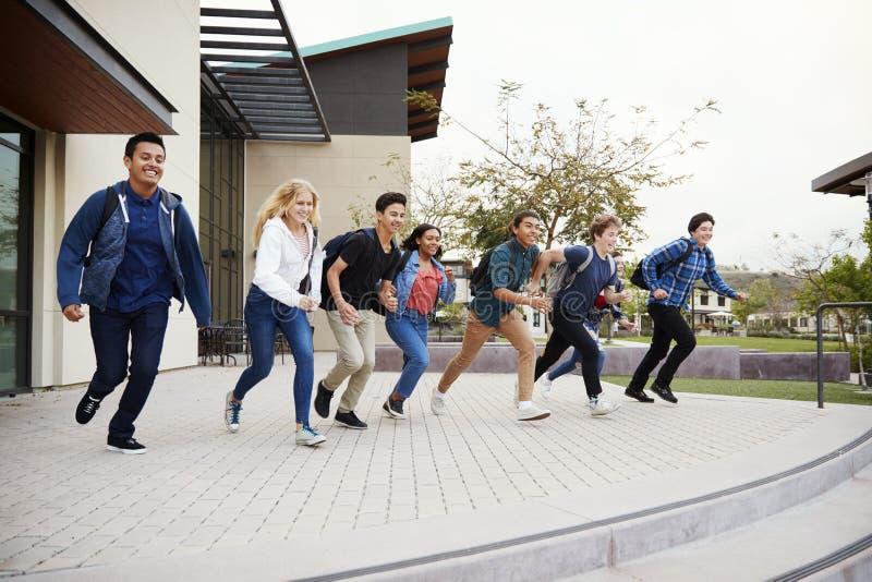 Grupo de estudiantes de la High School secundaria que corren hacia pasos fuera de edificios de la universidad fotografía de archivo libre de regalías
