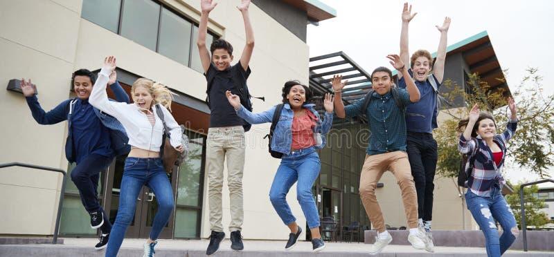 Grupo de estudiantes de la High School secundaria que saltan en aire fuera de edificios de la universidad fotos de archivo