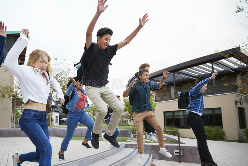 Grupo de estudiantes de la High School secundaria que saltan en aire fuera de edificios de la universidad imagen de archivo