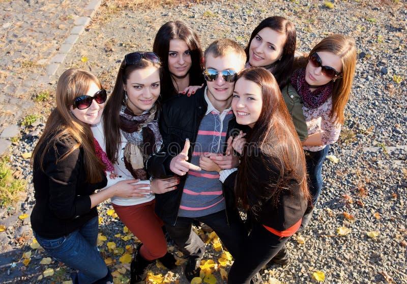 Grupo de estudiantes masculinos y femeninos en parque fotos de archivo