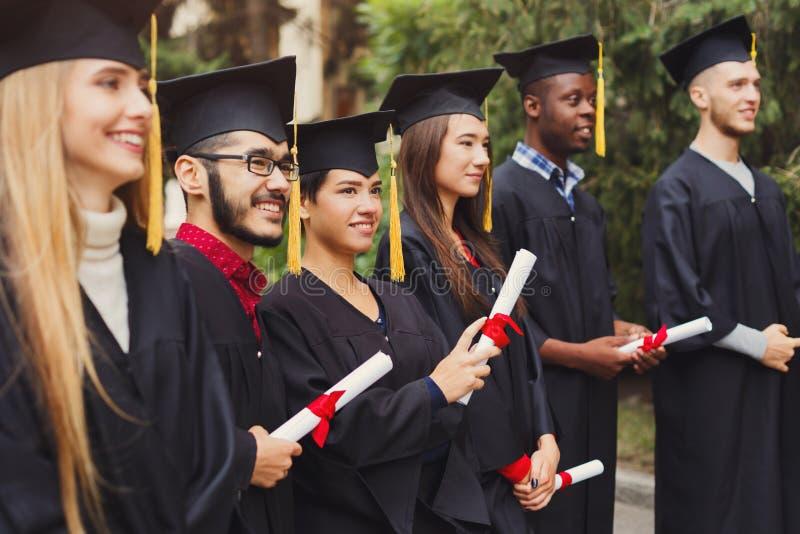 Grupo de estudiantes multiétnicos el día de graduación imagenes de archivo