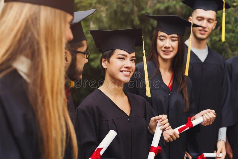 Grupo de estudiantes multiétnicos el día de graduación fotos de archivo