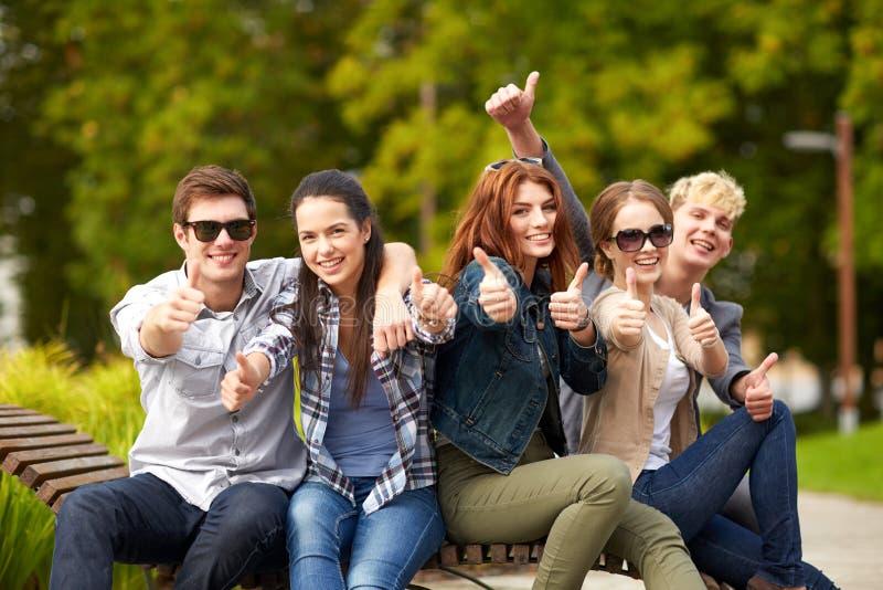 Grupo de estudiantes o de adolescentes que muestran los pulgares para arriba imagenes de archivo