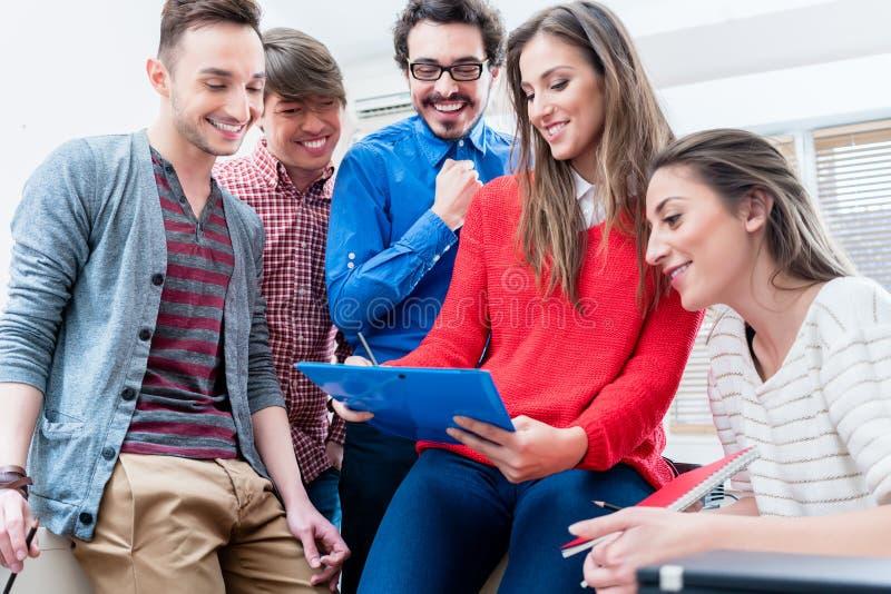 Grupo de estudiantes que aprenden junto en universidad imagen de archivo