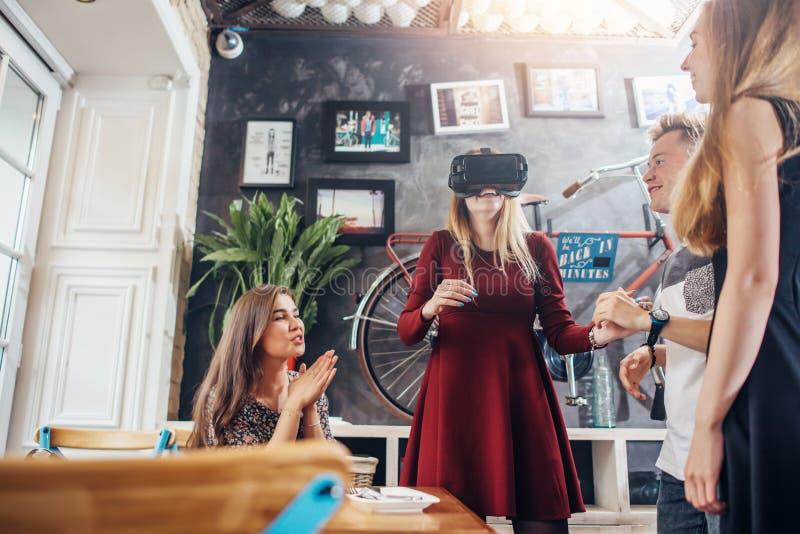 Grupo de estudiantes que distribuyen juntas las películas de observación en gafas de la realidad virtual 3d, el esperar de la muc imagen de archivo
