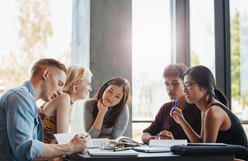 Grupo de estudiantes que hacen la asignación de escuela en biblioteca fotos de archivo