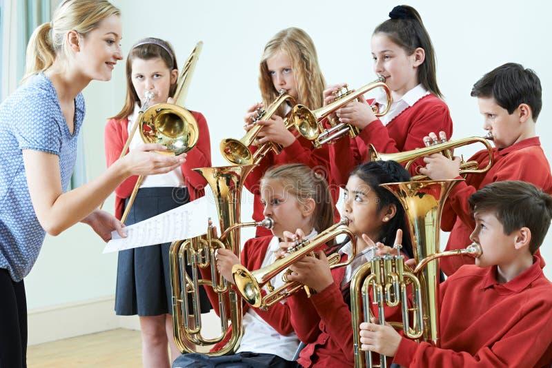 Grupo de estudiantes que juegan en orquesta de la escuela junto imagen de archivo
