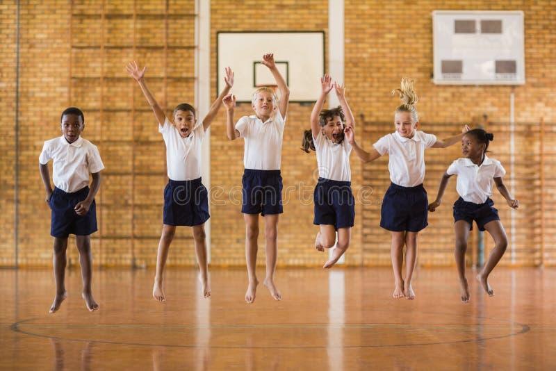 Grupo de estudiantes que saltan en gimnasio de la escuela imágenes de archivo libres de regalías
