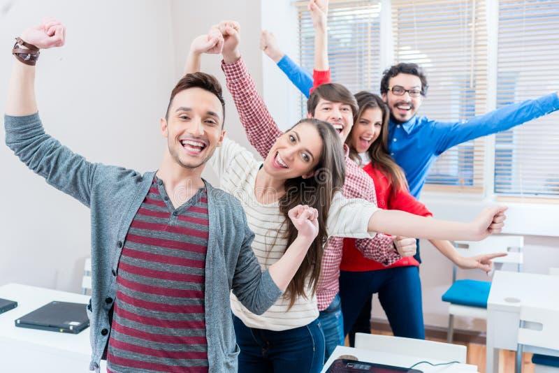 Grupo de estudiantes que se divierten en la universidad imagenes de archivo