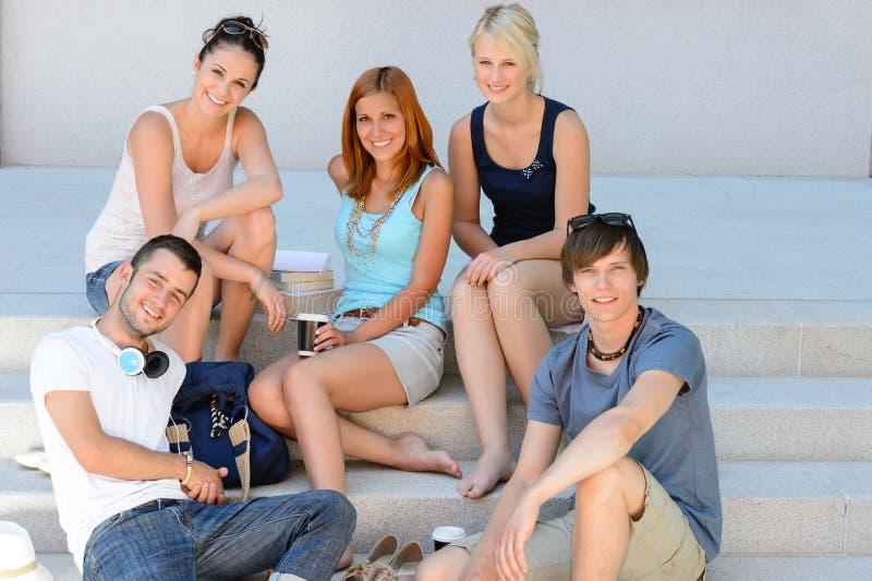 Grupo de estudiantes que se sienta en la sonrisa de las escaleras de la escuela fotos de archivo libres de regalías