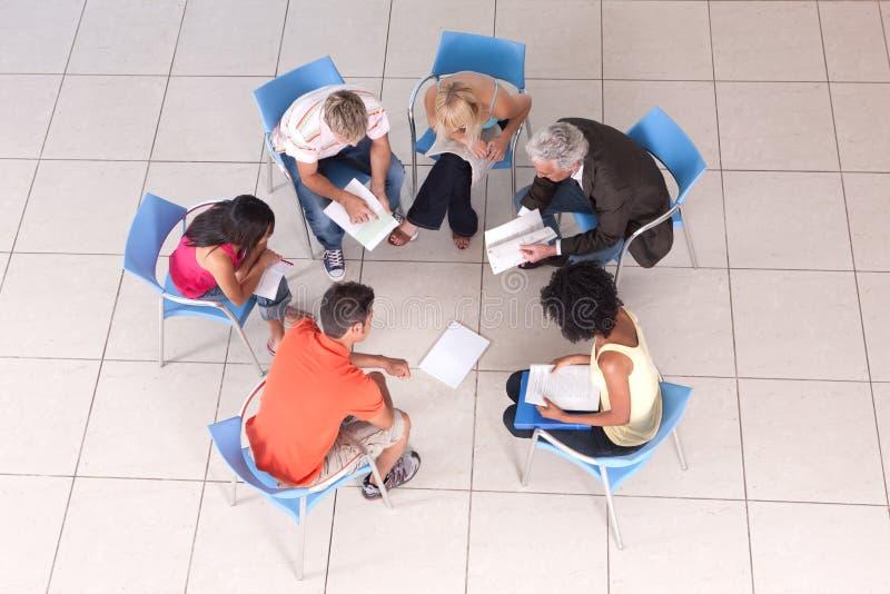 Grupo de estudiantes que se sientan con el conferenciante imagenes de archivo