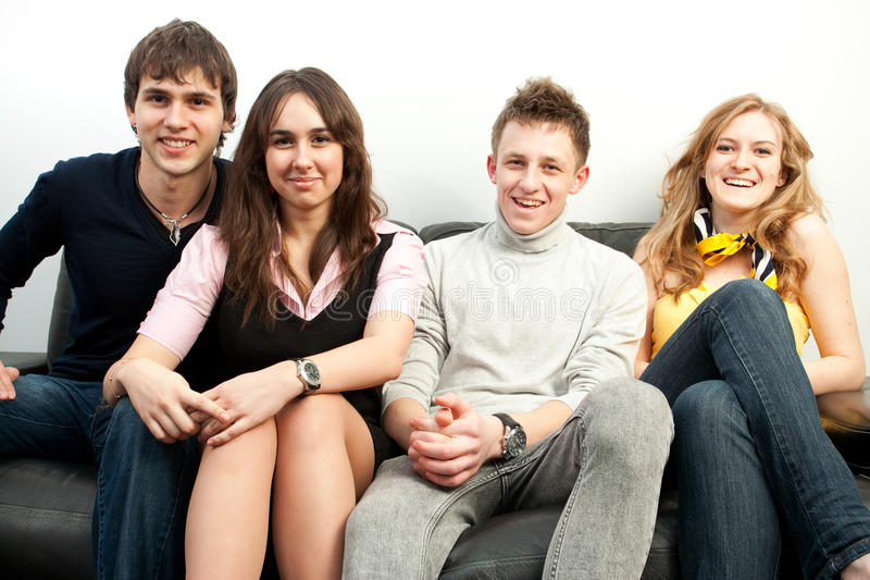 Grupo de estudiantes que se sientan en un sofá imágenes de archivo libres de regalías