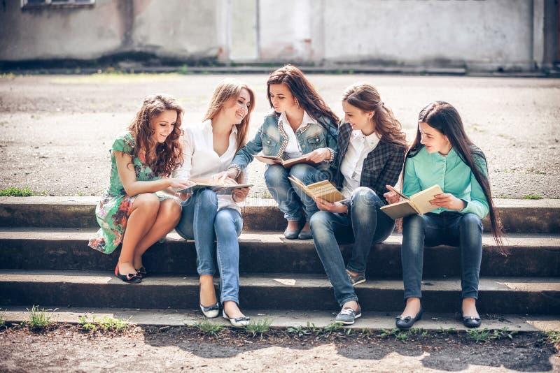 Grupo de estudiantes que sientan con los libros fotografía de archivo