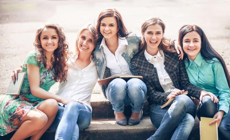 Grupo de estudiantes que sientan con los libros fotos de archivo