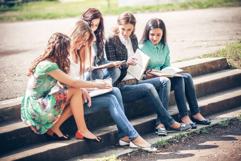 Grupo de estudiantes que sientan con los libros imagenes de archivo