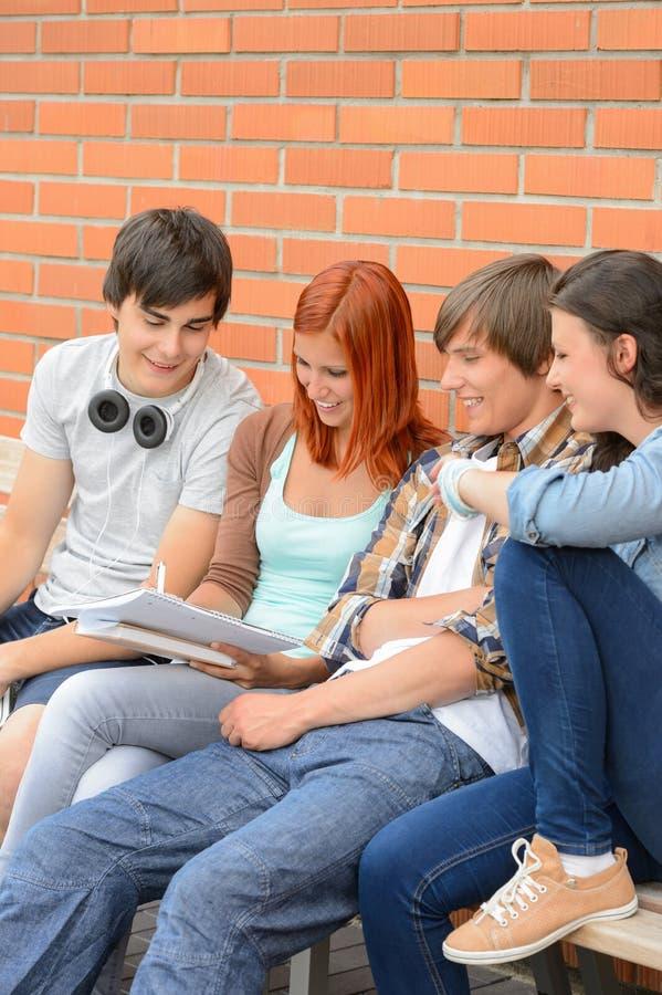 Grupo de estudiantes que sientan el banco fuera de la universidad fotos de archivo libres de regalías